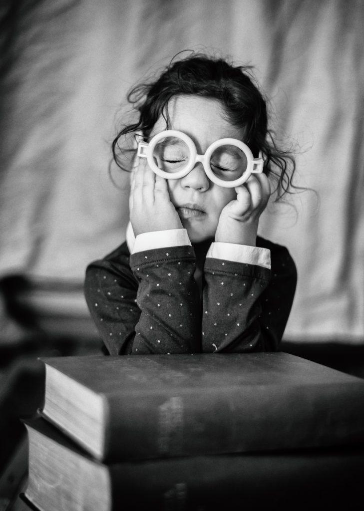 foto copii portret fetita cu ochelari care doarme pe carti